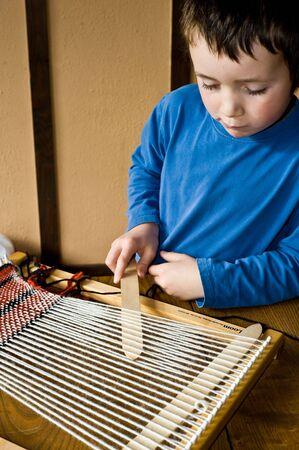 boy in blue preparing loom for weaving Imagens