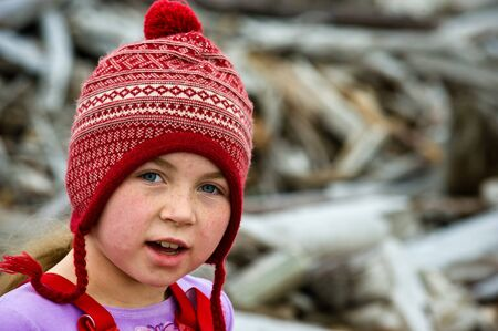 stocking cap: girl with redwhite stocking cap, freckles, on wood covered beach