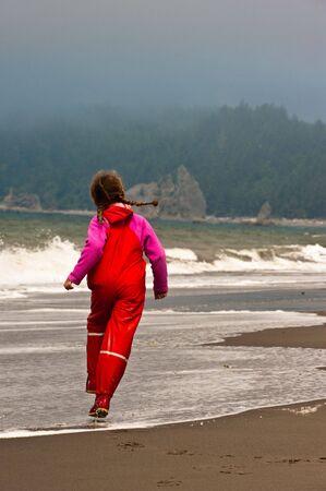 young girl skipping down ocean shore