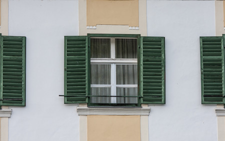 windows with open old green blinds, closed glass windwos,