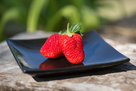 two strawberries on a black plate outdoors