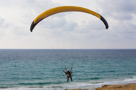Paratrooper parachute landing on the beach near the mediteranian sea photo