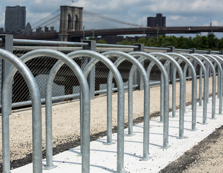 Steel circle to park bicycles, Brooklyn Bridge in New York City in background