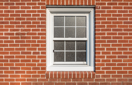white  window on a red brick wall, sun reflction on the glass