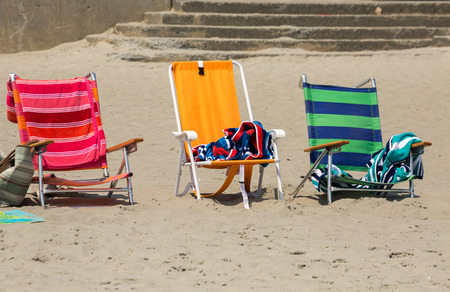 three colorful chairs on the sand, near the beach Stock Photo