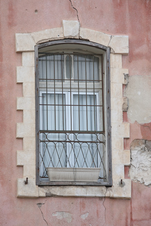 old window with bars, cracked wall background