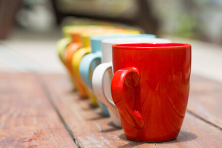 set of colorful mug cups on a old wooden table, blured background Stock Photo
