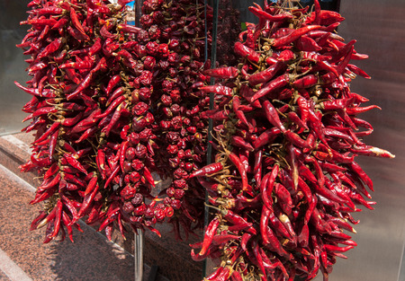 Strings Dried Red Hot Chili Peppers hanging outdoors