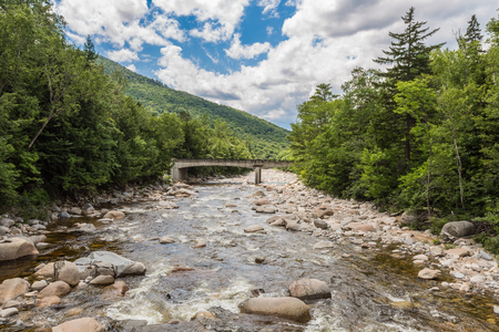 River through forest near the White Mountains, a bridge in background