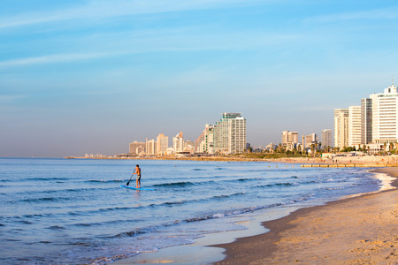 Young man surf in the shore of Tel Aviv Israel, at sunset