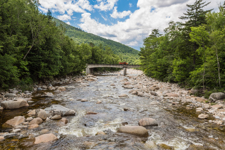 River through forest near the White Mountains  New Hampshire, a bridge in background