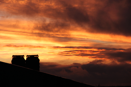 roofs and chimneys at sunset with clouds and smog