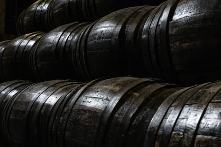 old wooden barrels for whiskey or wine stacked in the cellar