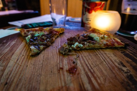 Sliced pizza and candle on wooden table