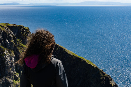 One woman standing on the edge of a high irish cliff with ocean in the background. Banco de Imagens - 124983784