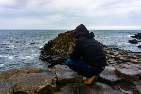 Man is looking at the Atlantic Ocean. Giants Causeway in Northern Ireland Banco de Imagens