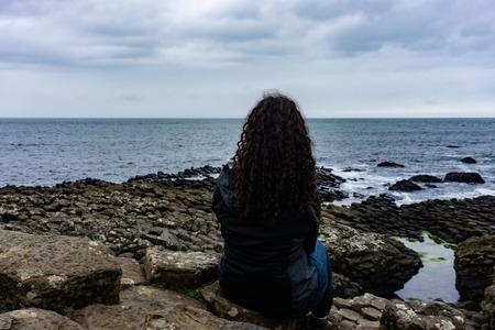 Girl is looking at the Atlantic Ocean. Giants Causeway in Northern Ireland Banco de Imagens