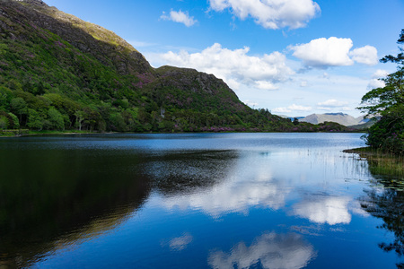 Lake landscape with mountain peaks covered in lush vegetation, Pollacapall Lough in, Connemara, Galway, Ireland.