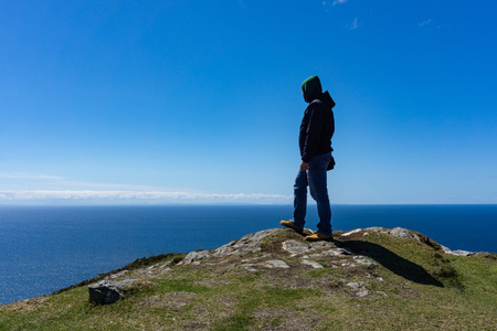 One man standing on the edge of a high cliff with ocean and clouds in the background. Taken in Inishmore, Ireland