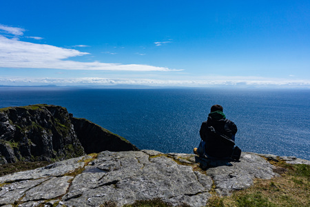 One man standing on the edge of a high cliff with ocean and clouds in the background. Taken in Inishmore, Ireland Banco de Imagens - 124983949