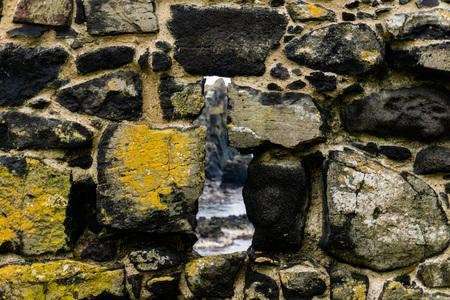 sea seen through stone wall in Ireland 스톡 콘텐츠