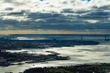 Aerial view of Manhattan skyline from the sky on a cloudy day, New York City.