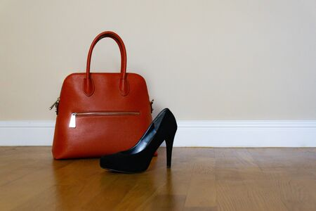 Black high heel women shoes and a orange bag on parquet