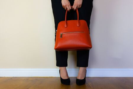 a woman standing with her legs crossed holding on to her bag. Reklamní fotografie