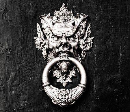 Chinese demon golden door handle - knocker in a black and white wooden door 写真素材
