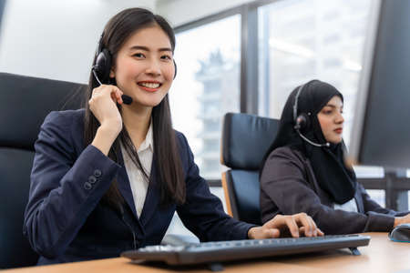 Happy smiling asian woman call center and operator wearing headsets working on computer and talking with customer with her service mind Standard-Bild