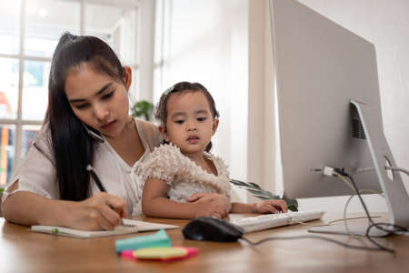 Work from home concept. Mother and daughter using a computer and internet during mother working from home