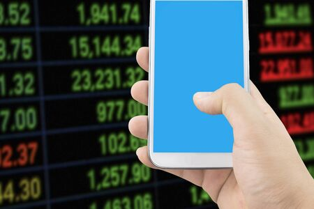 stock ticker board: Hand Holding Smartphone .  Blur Colored ticker board on black . Smart Stock Investment  Digital Marketing concept