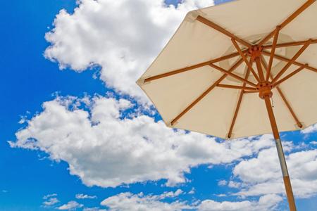umbella: Beach umbella on blue sky with clouds