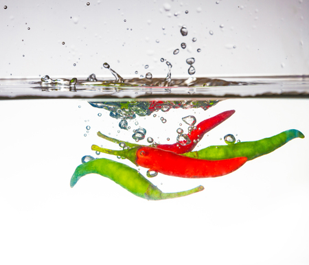 hot chili pepper dropped into water with splash photo