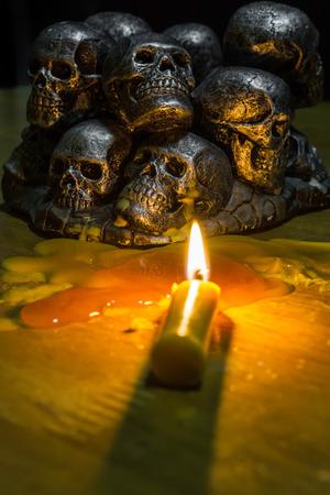 schedels met een kaars branden op houten achtergrond in de duisternis Stockfoto