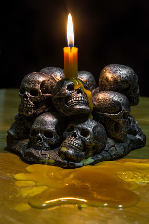 diabolic: skulls with candle burning on wooden background in the darkness