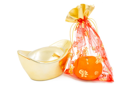concept image of the chinese new year - Gold Ingot and mandarin orange in the red auspicious bag photo
