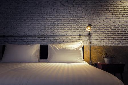 cama: Primer plano de una cama con la luz de la lámpara
