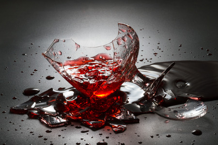 Pouring red wine on broken glass.