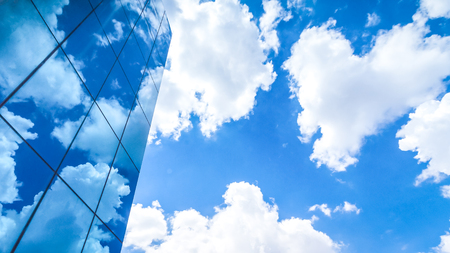 filming point of view: clouds reflected in the many mirrored facets of a modern office building Stock Photo