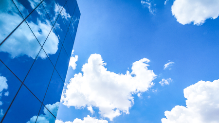 facets: clouds reflected in the many mirrored facets of a modern office building Stock Photo