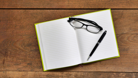 chronicle: Top view workspace with blank notebook ,glasses and pen on wooden table background . Stock Photo