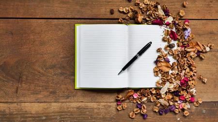 flores secas: Vista superior del espacio de trabajo con el cuaderno en blanco, pluma y flores secas en el fondo de la tabla de madera.