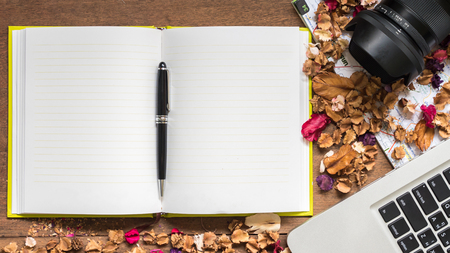 note booklet: Top view workspace with blank notebook,laptop,camera and dried flowers on wooden table background . Stock Photo