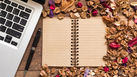 memoir: Top view workspace with notebook,pen,laptop and dried flowers on wooden table background . Stock Photo