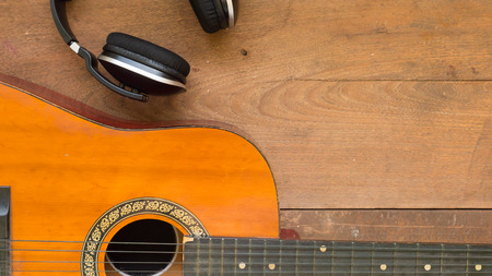 free space: Top view workspace with headphone and acoustic guitar on wooden table background .Free space for your text.