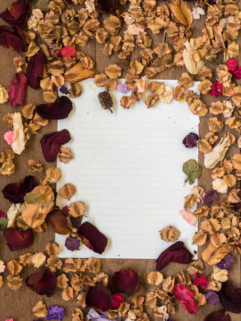 memoir: Top view workspace with blank paper and dried flowers on wooden table background .