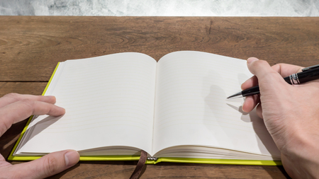 jot: Hands with pen writing on notebook. Stock Photo