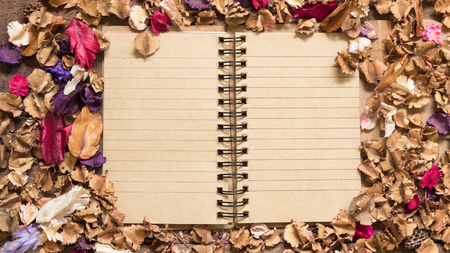 memoir: Top view workspace with blank notebook and dried flowers on wooden table background .