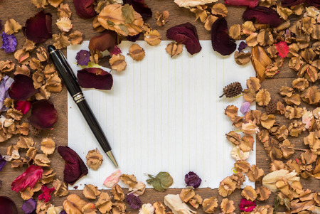 chronicle: Top view workspace with blank paper,pen and dried flowers on wooden table background .